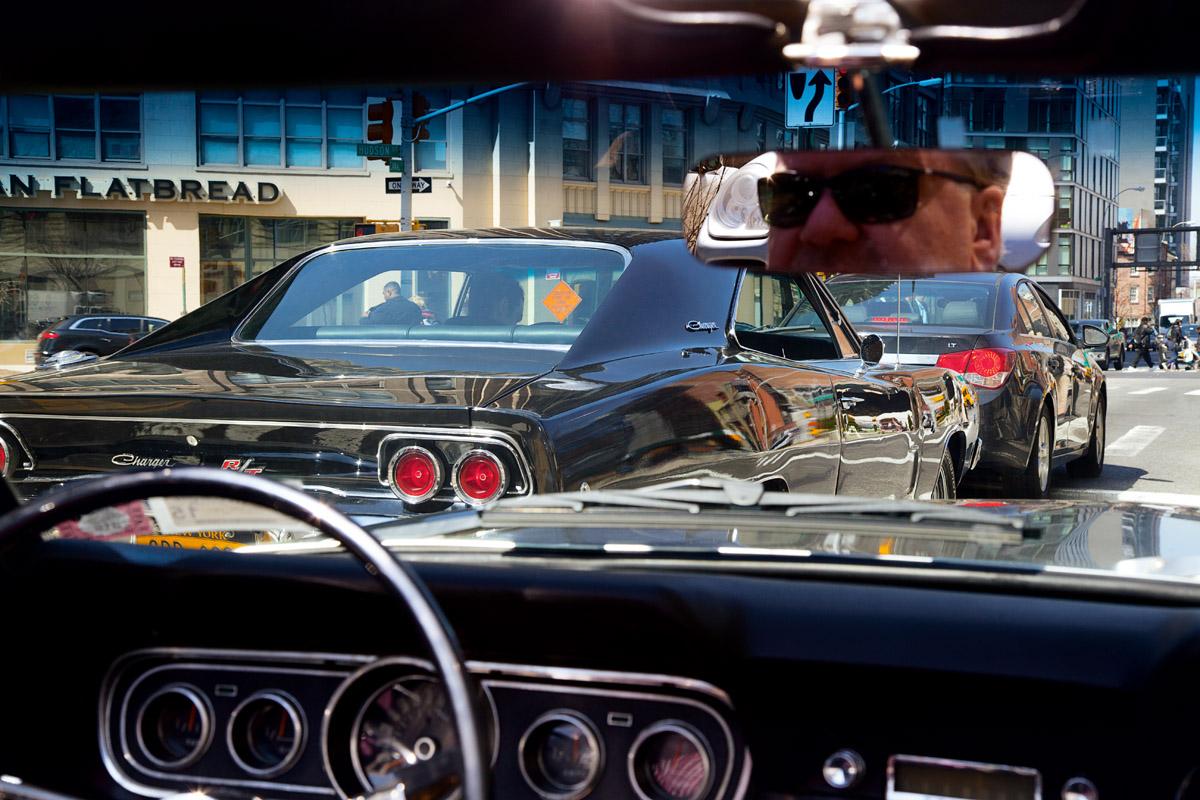Blick aus einem Ford Mustang Cabrio des Manhattan Classic Car Club auf das Heck eines Dodge Charger