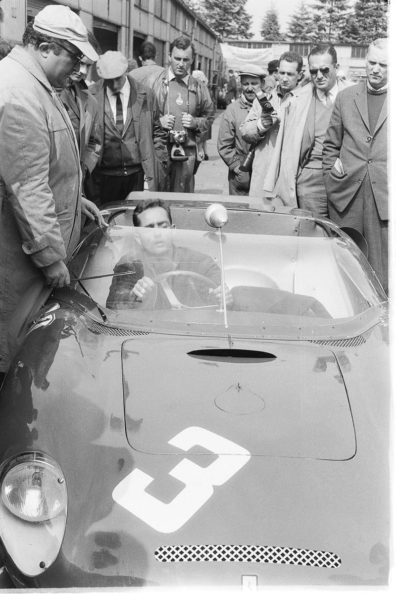 Phil Hill in seinem Ferrari mit vielen Männern um den Wagen herum