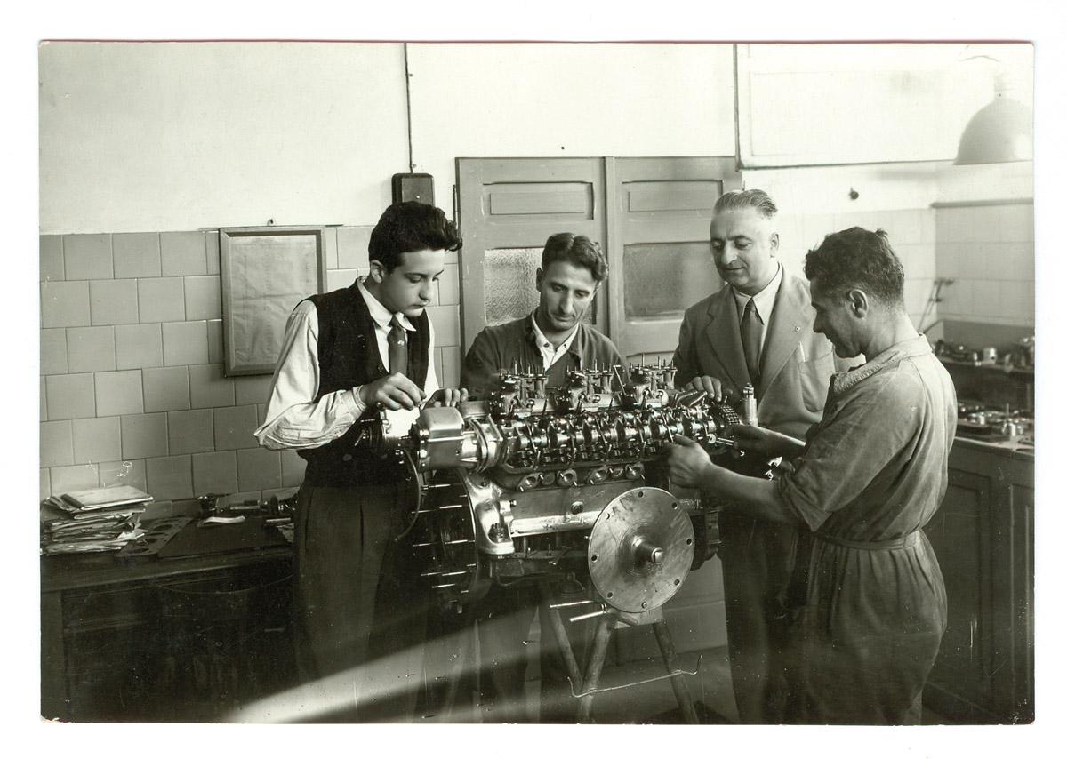 Dino Ferrari bei der ARbeit an einem V12. Mit dabei: zwei Mechaniker und sein Vater Enzo Ferrari.