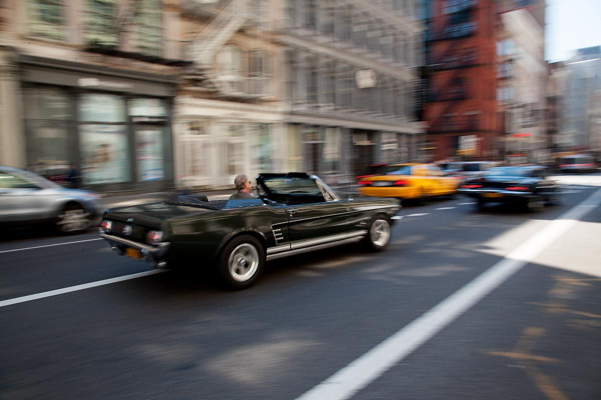 Ford Mustang Cabrio fahrend von schräg hinten