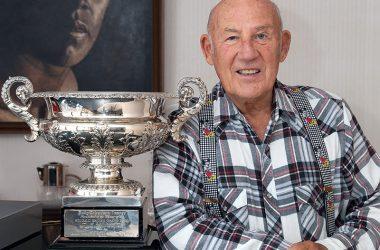 Stirling Moss posiert neben einem Pokal