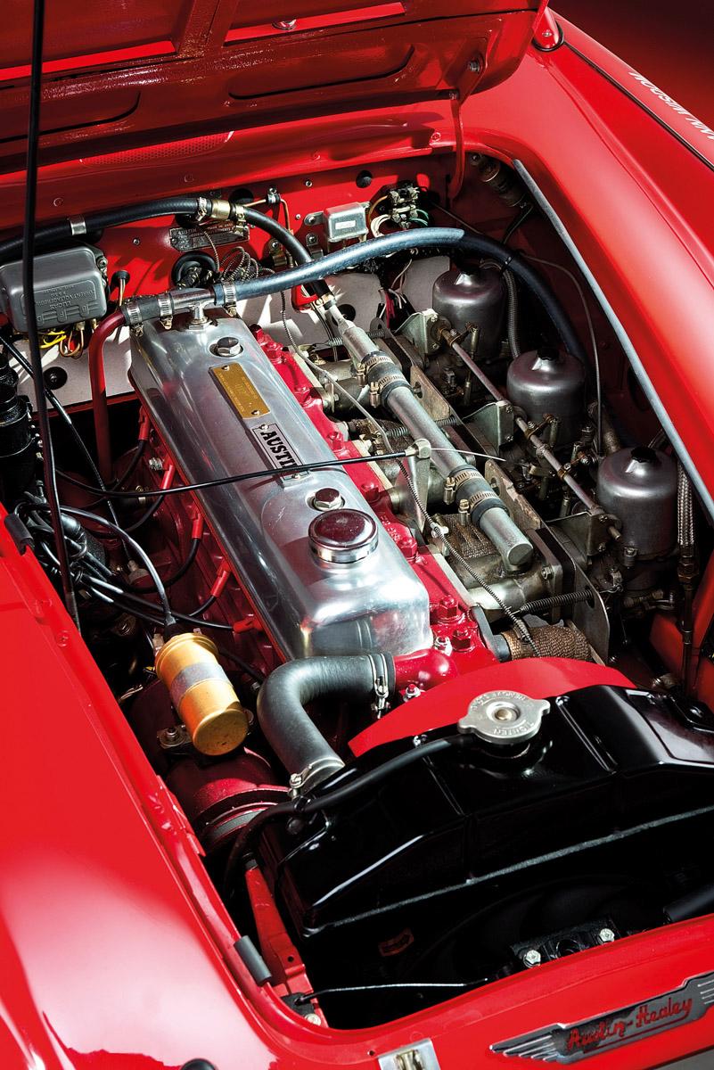 Motor des Austin-Healey 3000 und drei Austin-Healey 3000 stehend